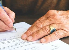 elderly person signing a form
